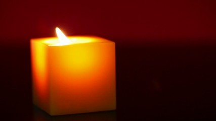 Burning candle against red background