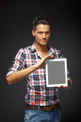 portrait of a young man holding a digital tablet over a grey bac