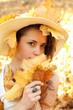 Piękna dziewczyna w kapeluszu i jesienne liście.