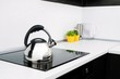 Steel kettle in modern kitchen with induction stove - 57910990