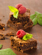 Chocolate brownies with raspberries on wooden background
