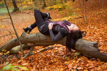 Beautiful girl is relaxing in a park in autumn