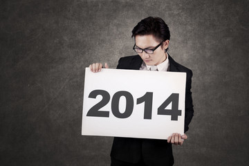Businessman holding board The New Year 2014