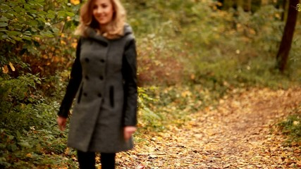 blond elegant woman walking in park