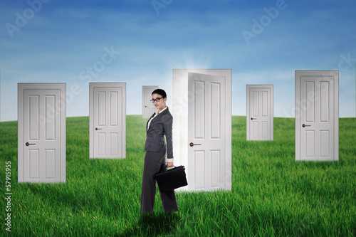 Businesswoman standing in front of opportunity doors