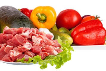 Fresh raw meat and vegetables isolated on white