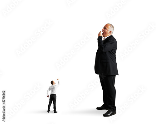 small man showing fist to big bored businessman