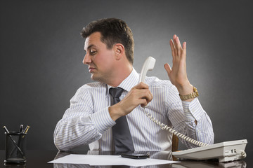 Businessman having a talk to the hand gesture during phone call