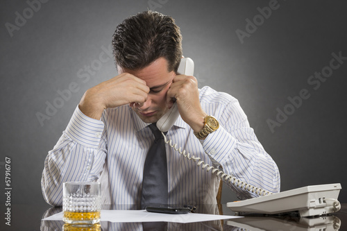 Stressed businessman with headache during a phone call
