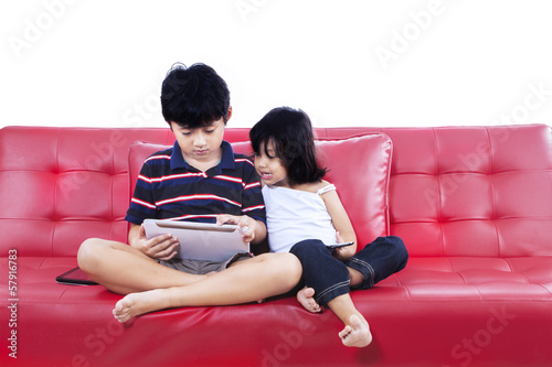 Children using electronic tablet together