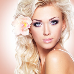 face of a beautiful woman with white flower in hairs