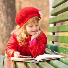 Little girl reading a book  in the park.