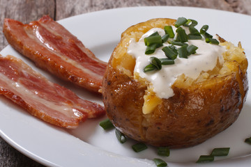 baked potato filled with sour cream and slices of fried bacon