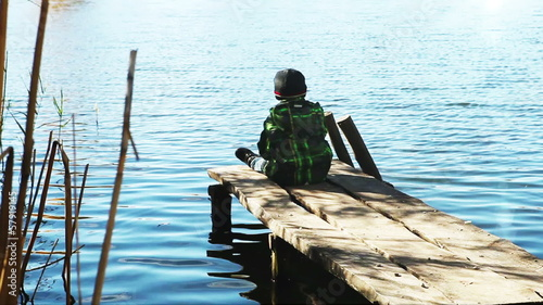 Alone boy throw rocks in the lake water