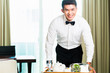 Asian Chinese room waiter serving guests food in hotel