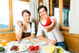 Junges Paar auf Berg in Almhütte isst