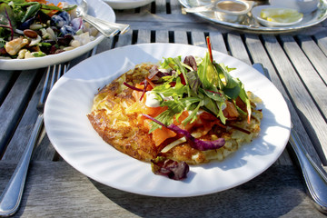 Potato rosti on a plate with smoked salmon and salad.