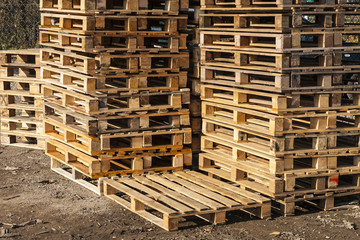 Wooden transport pallets in stacks ready for delivery.
