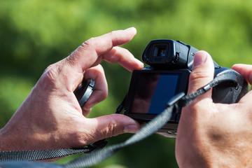 Männerhände halten eine Fotokamera