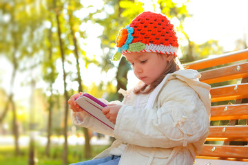 Happy child holding tablet PC in autumn park