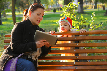 Happy mother and her child looking at tablet PC in park