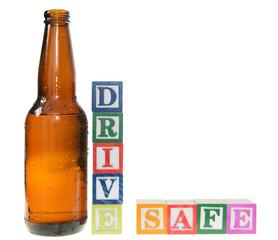 Letter blocks spelling drive safe with a beer bottle
