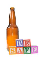 Letter blocks spelling be safe with a beer bottle
