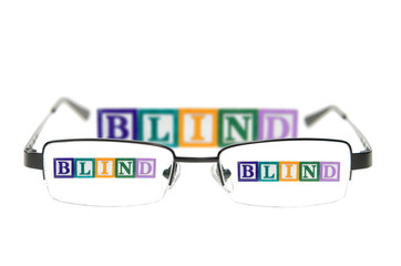 Letter blocks spelling blind through a pair of glasses