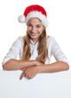 Lachende Frau mit Nikolausmütze zeigt auf Werbetafel