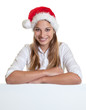 Beautiful woman with christmas hat on a signboard