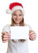 Lachende Frau mit Nikolausmütze zeigt Karte