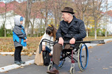 Woman and her son helping a disabled old man