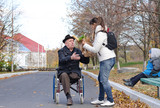 Mother helping her elderly disabled father