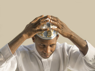 Young african man putting on  a traditional celebration hat