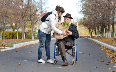 Man in a wheelchair being helped with groceries