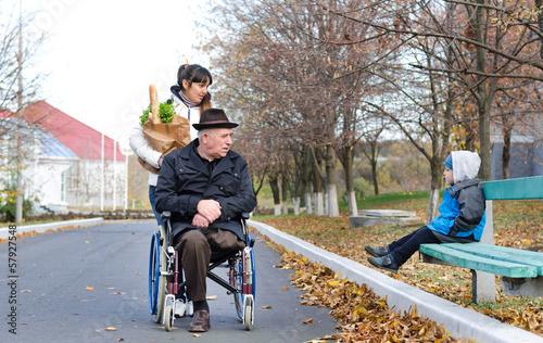 Disabled man and his carer chat to a little boy