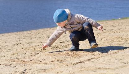 Cute little boy playing on a sandy beach