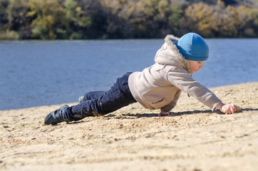 Young boy playing on beach sand at the coast