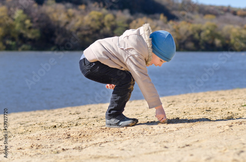 Small boy drawing in the beach sand