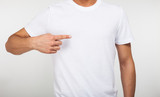 Man pointing his finger on a blank t-shirt