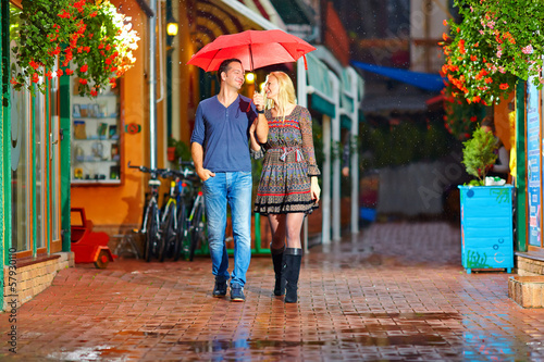happy couple walking under the rain on cozy colorful street