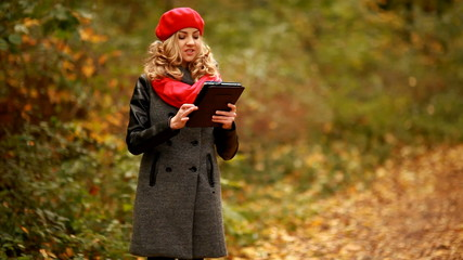 Young blond girl with tablet in park