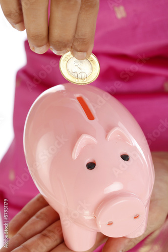 Hand inserting a coin into piggy bank
