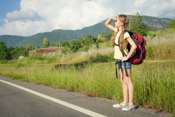 one girl with backpack walking on the road