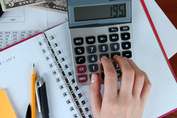 Woman hand counting on calculator on worktable background