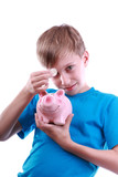 Beautiful funny blond child puts a coin into a pink piggy bank