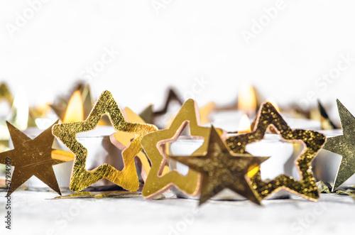 Weihnachtliche Dekoration: Goldsternchen und Kerzenlicht