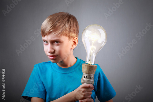 Beautiful funny child holding a big vintage light bulb