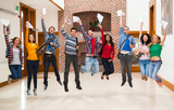 Happy students jumping for joy holding exam results in a hallway