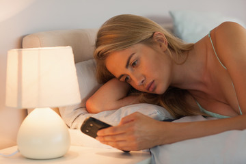 Blonde woman lying in bed sending a text by lamp light